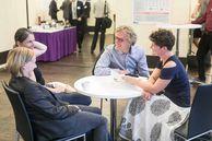 Vier Personen sitzen an einem Tisch, unterhalten sich und lachen.